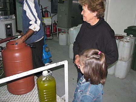 γιαγιά και εγγονή βλέπουν το λάδι να βγαίνει